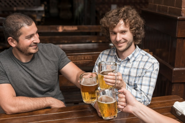 Men celebrating with friend in bar