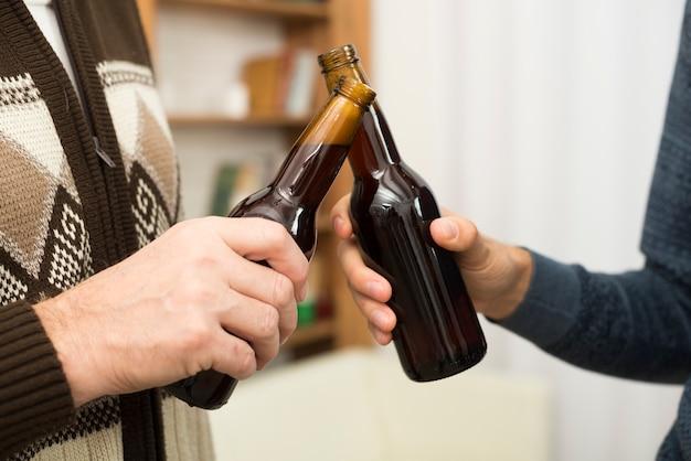 Men clanging bottles of alcohol in room