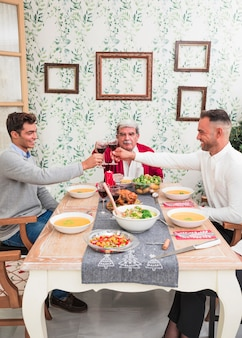 Men clanging glasses at festive table