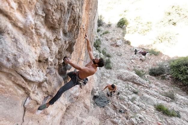Uomini che si arrampicano su una montagna con equipaggiamento di sicurezza