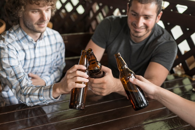 Men clinking bottles with anonymous friend