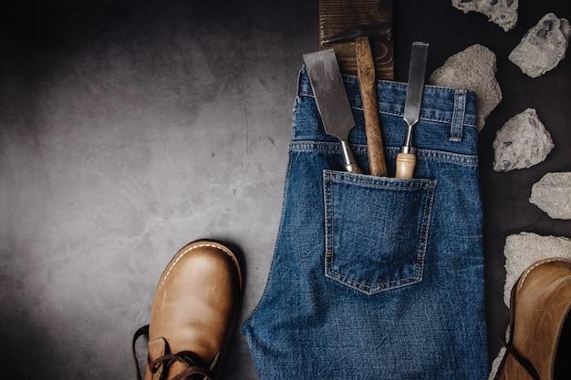 Концепция мужской одежды. джинсовые штаны лежали на цементном полу в окружении кожаной обуви, бетона и разнорабочих инструментов. темный тон