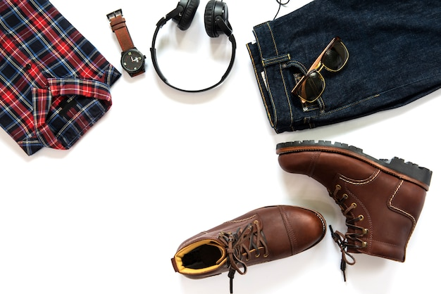 Men clothing set with brown boots, shirt, jeans, watch and earphone isolated on white background. top view, copy space