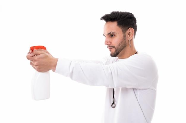 白い背景の上のブロードライヤーで髪をとかして乾かす男性