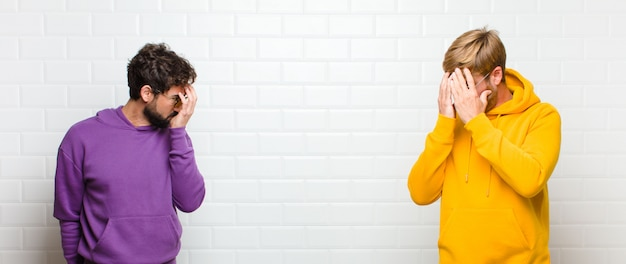 Men covering eyes with hands with a sad, frustrated look of despair, crying, side view