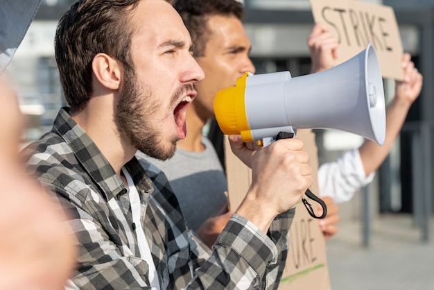 Men demonstrating together with megaphone