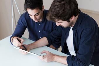 Men discussing data on tablet