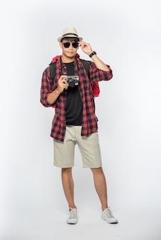 旅行用の服を着て、眼鏡と帽子をかぶってバッグを持ってカメラを持っている男性