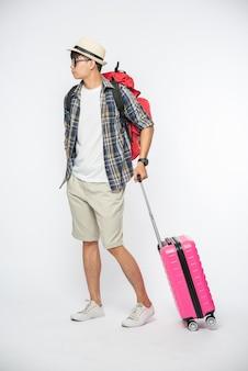 旅行用の服を着て、眼鏡と帽子をかぶって、バッグと荷物を運ぶ男性