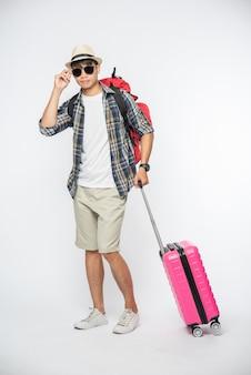 여행용 옷을 입고 안경과 모자를 쓰고 가방과 수하물을 운반하는 남성
