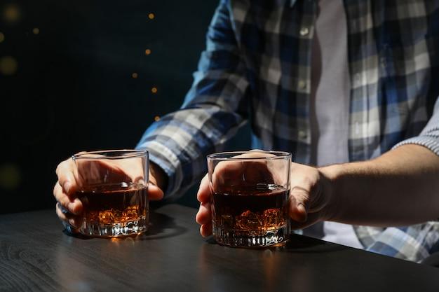 남자는 바에서 위스키를 마시고 닫습니다. 흐릿한 조명 바에서 위스키를 마시는 남자를 닫습니다. 흐릿한 조명