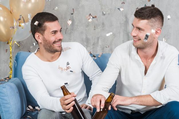 Men drinking beer on sofa