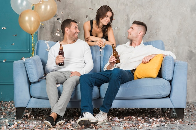 Men drinking beer and talking to woman