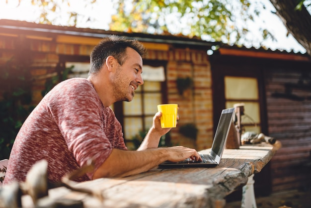 Men drinking coffee and using laptop at backyard patio