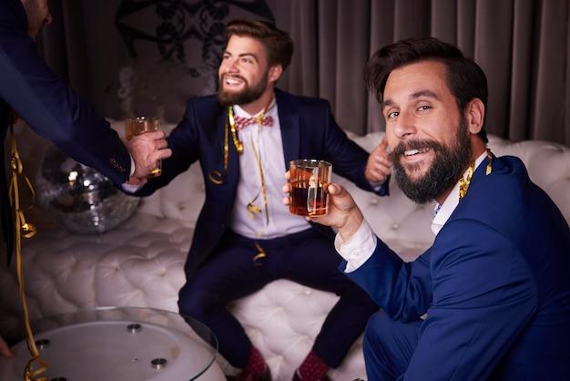 Uomini che bevono whisky al night club