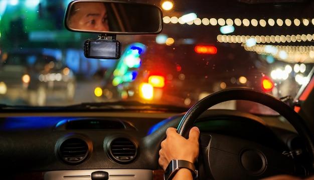 Men driving a car at night.