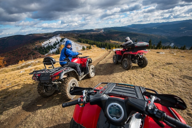 Men driving quad bikes in front on top of mountain