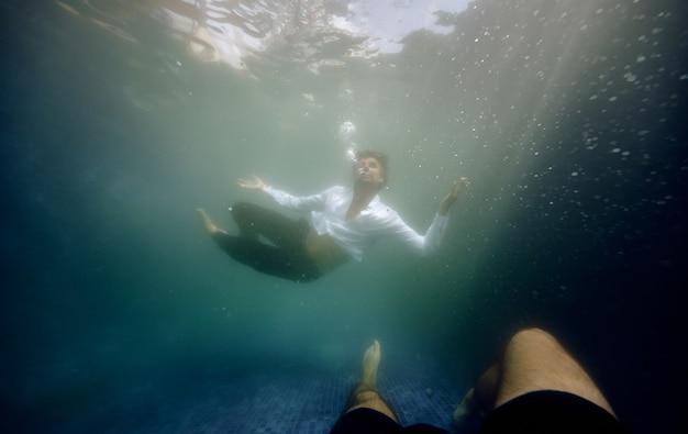 プールの水に溺れる男性