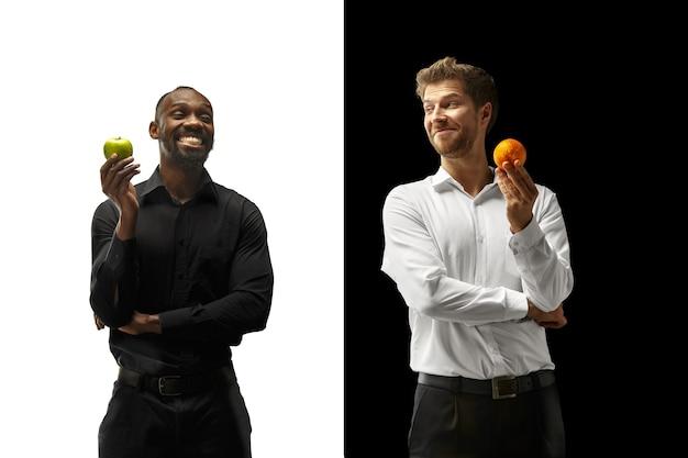 黒と白の背景に新鮮な果物を食べる男性。幸せな笑顔のアフロと白人男性。健康的な食事と食事の概念