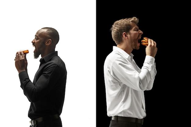 黒と白の背景にハンバーガーとドーナツを食べる男性。幸せなアフロと白人の男性。ハンバーガー、速くて不健康な食べ物のコンセプト