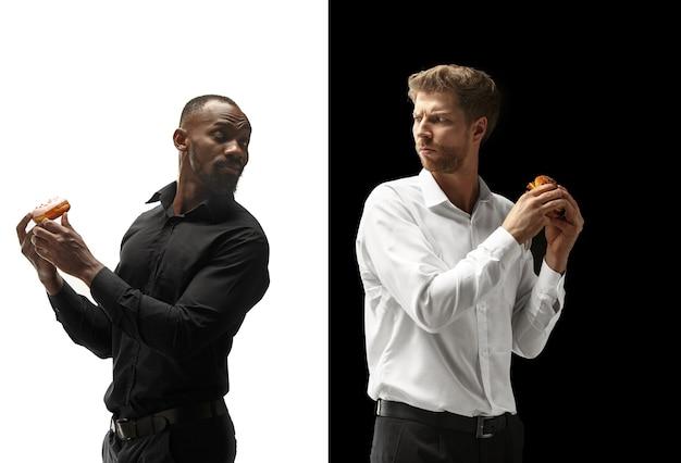 黒と白の背景にハンバーガーとドーナツを食べる男性。幸せなアフロと白人男性。ハンバーガー、速くて不健康な食べ物のコンセプト