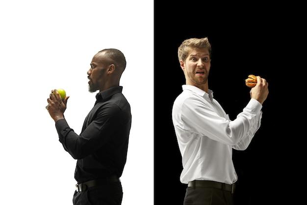 黒と白の背景にハンバーガーと新鮮な果物を食べる男性。幸せなアフロと白人の男性。ハンバーガー、速くて健康的で不健康な食品のコンセプト