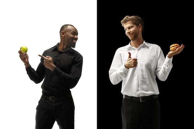 黒と白の背景にハンバーガーと新鮮な果物を食べる男性。幸せなアフロと白人男性。ハンバーガー、速くて健康的で不健康な食品のコンセプト