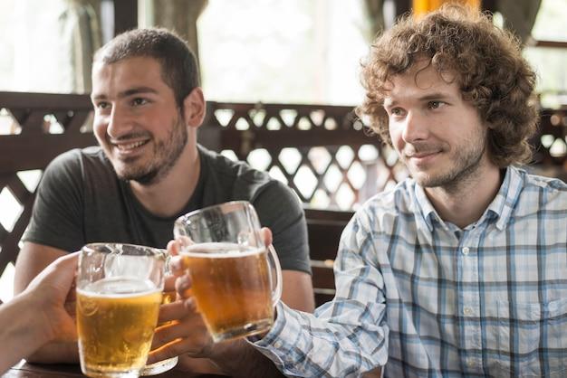 Men enjoying beer and clinkingmugs