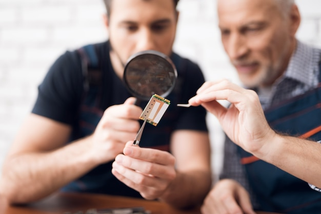 Men examine pc component with magnifying glass.