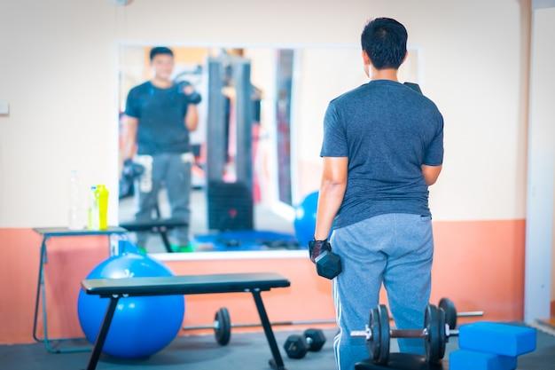 Men exercise dumbbell in gym exercise fitness club center