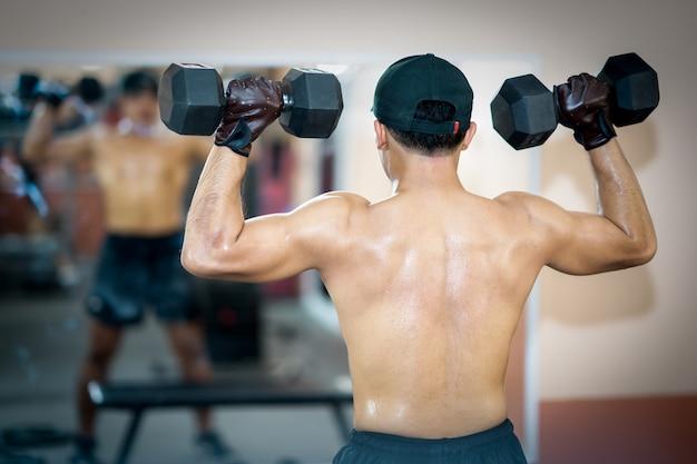 Men exercise dumbbell in gym fitness