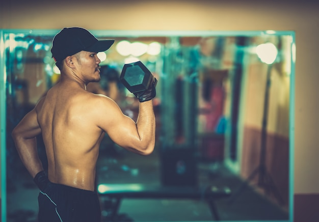 Men exercise dumbbells in gym fitness exercise club center on mirrors background