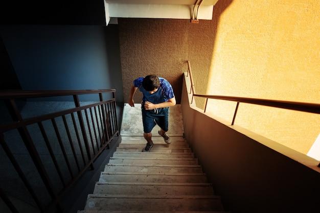 朝の日差しの中でコンクリートの階段を上り下りして運動する男性。