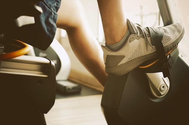 Мужчины тренируются на велотренажере в тренажерном зале. в лучах утреннего солнца.