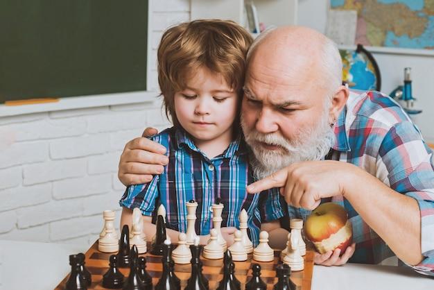 孫にチェスの親と親子関係を教える男性家族の祖父