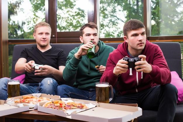 Tifosi di uomini che guardano il calcio in tv e bevono birra. tre uomini che bevono birra e si divertono insieme al bar
