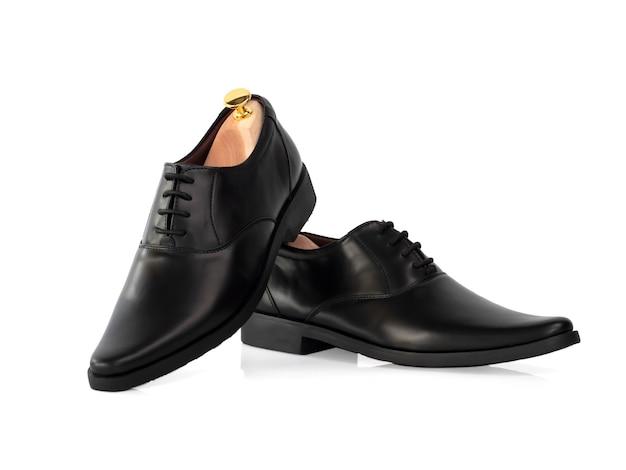 男性は白で隔離の靴の木(形状サポーター)と黒革オックスフォードシューズをファッションします。