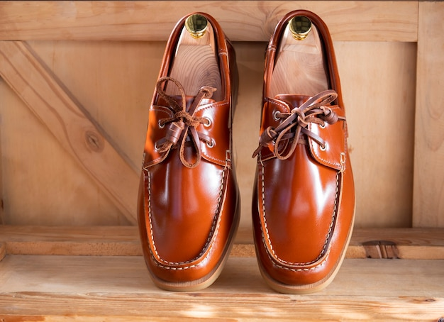 Men fashion boat shoes leather on wooden background.