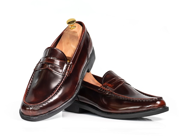 Men fashion brown polished leather collection loafer shoes with shoe tree (shape supporter) isolated on white.
