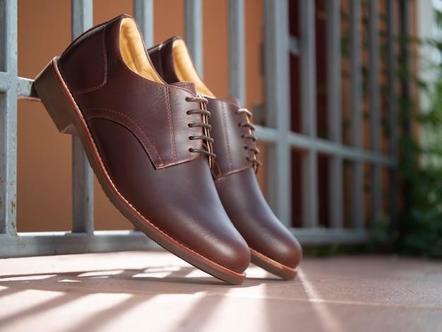 Мужская модная коричневая кожаная обувь на полу.