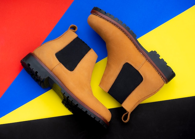 Men fashion chelsea boots isolated on colorful background. top view
