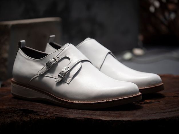 Men fashion double monk strap white shoes leather on wood.