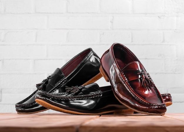 Men fashion tassel loafer shoes on white brick background.