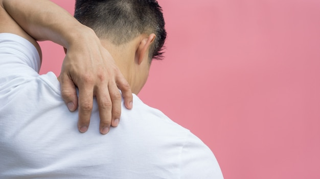 Men feeling pain in his shoulder on a pink background.