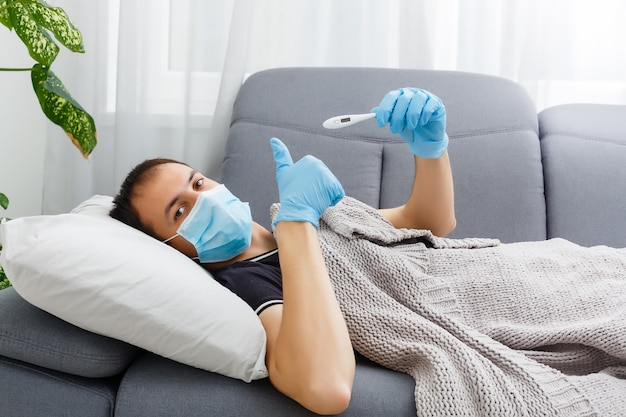 Men feels cold and sick from corona virus. he uses a thermometer to check the body temperature