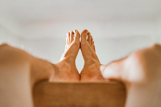 男性の足が互いに触れます。裸の男性の足は茶色のバーに横たわります。