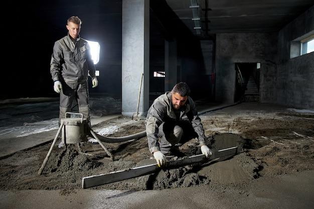 コンクリートで床を埋める男性