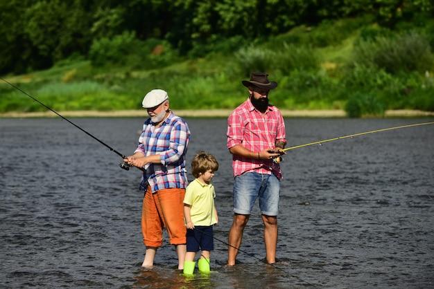 여름 시간에 강에서 낚시하는 남자 할아버지 아버지와 아들이 강에서 플라이 낚시를 하고 있다
