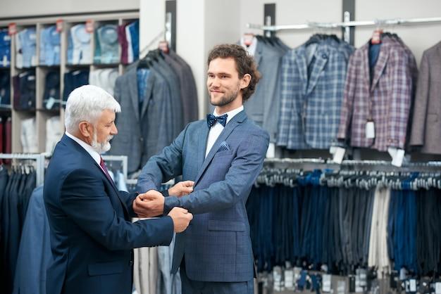 상점에 세련된 의상을 입히는 남자.