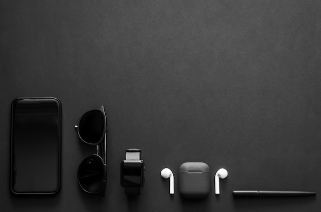 Men gadgets in modern lifestyle on dark background for minimalist flat lay black concept.